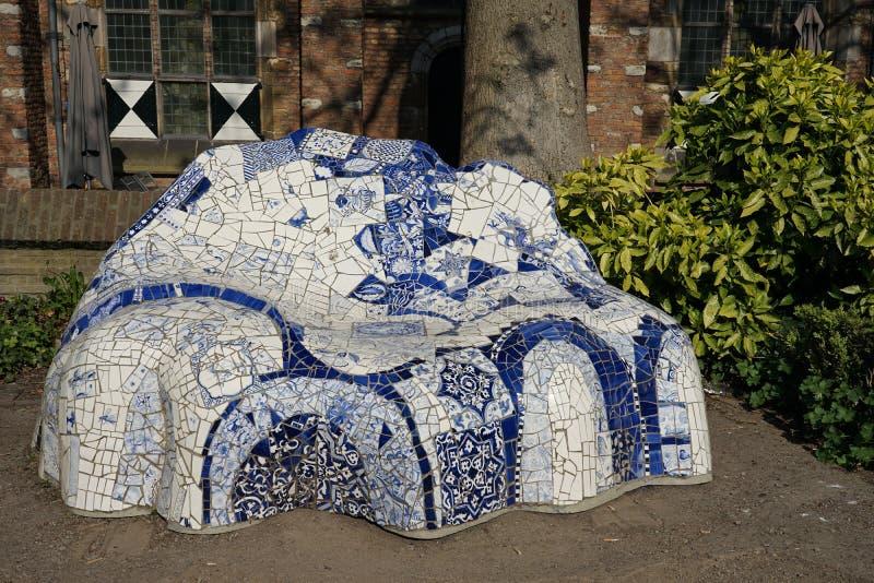Louça de Delft, os Países Baixos - 21 de abril de 2019: O sofá com as telhas azuis da louça de Delft no jardim de Het Prinsenhof  imagem de stock