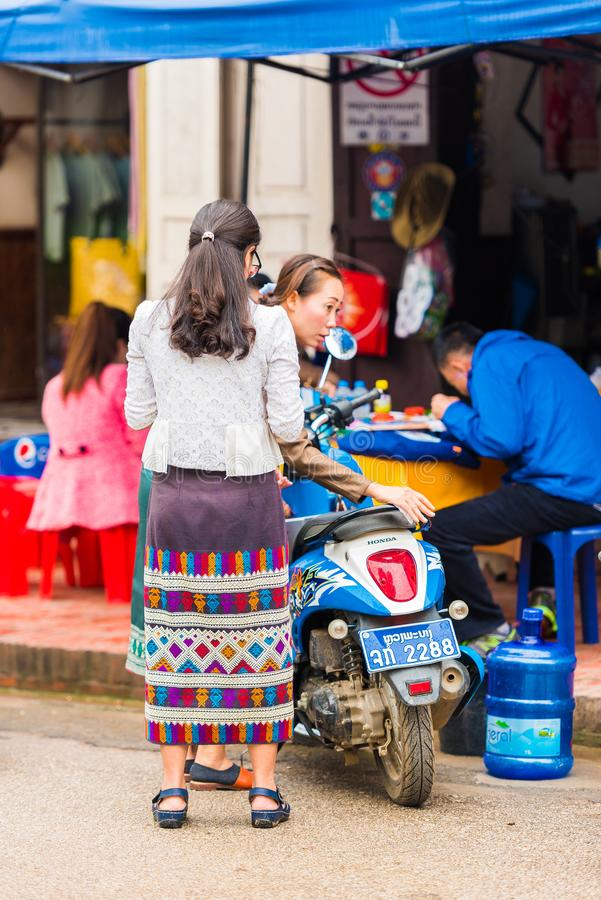 LOUANGPHABANG,老挝- 2017年1月11日:有一辆摩托车的妇女在城市街道上 垂直 库存照片