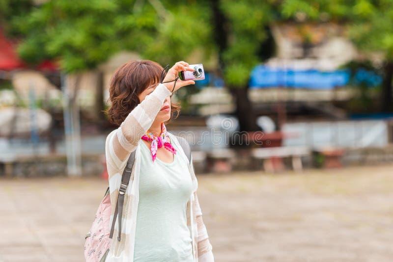 LOUANGPHABANG, LAOS - 11 DE ENERO DE 2017: Turista de la mujer que toma las imágenes de los alrededores Copie el espacio para el  fotos de archivo libres de regalías
