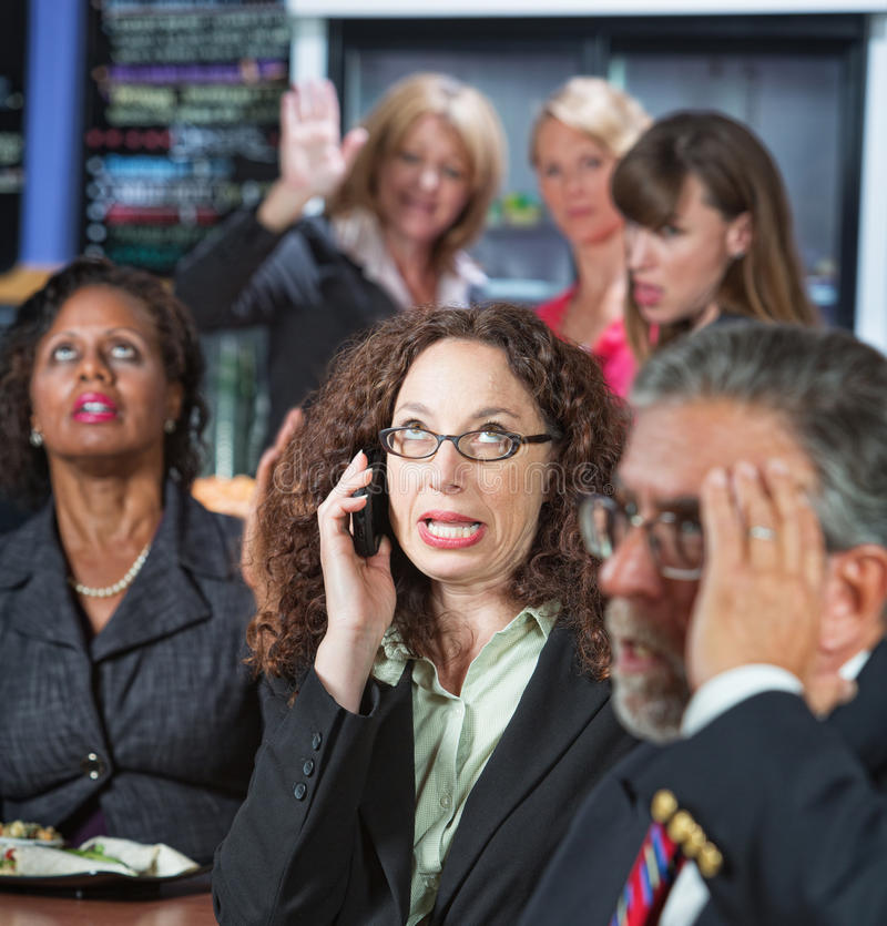 Loud Coworker on Phone. Loud women on cell phone in cafeteria with coworkers stock photo