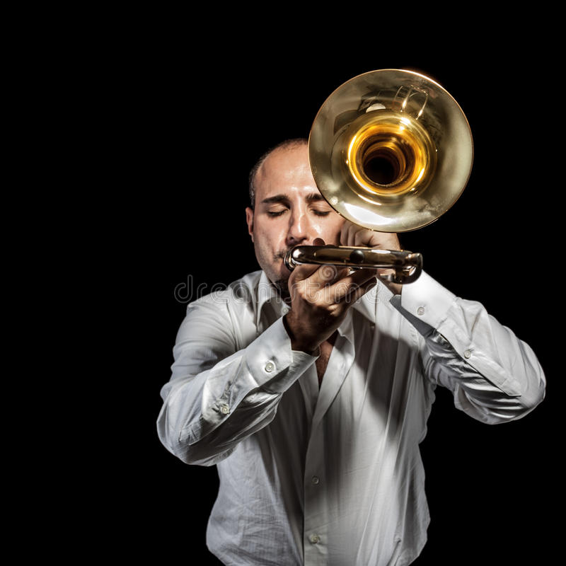 Loud jazzer. A young jazzer with a trombone over black background stock image