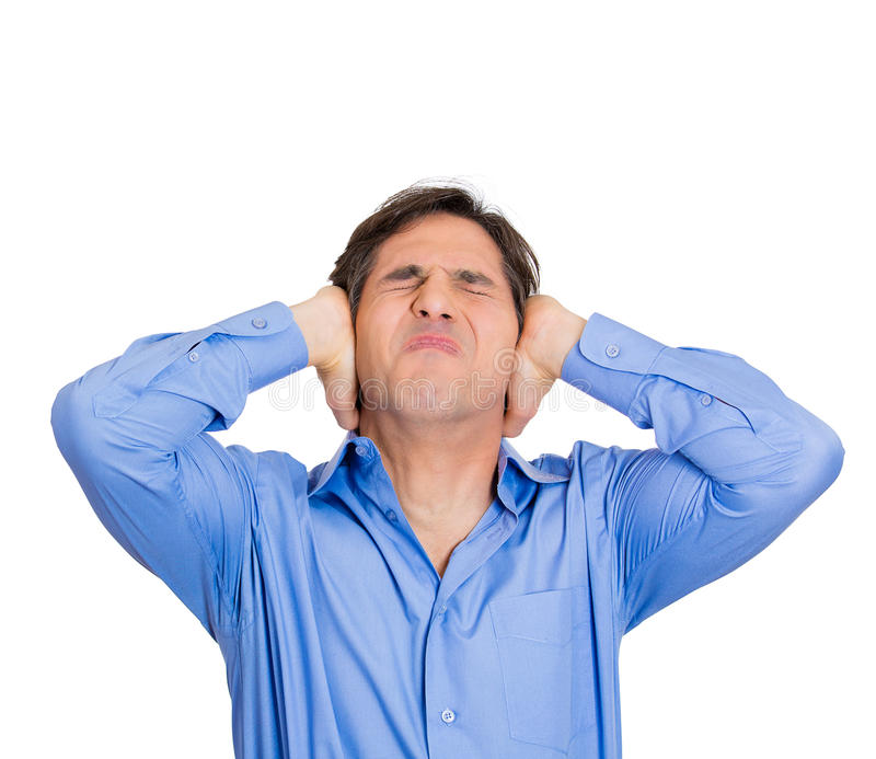 Loud noise. Closeup portrait young, angry, unhappy, stressed man covering his ears, looking up to say, stop making loud noise it's giving headache, isolated royalty free stock images