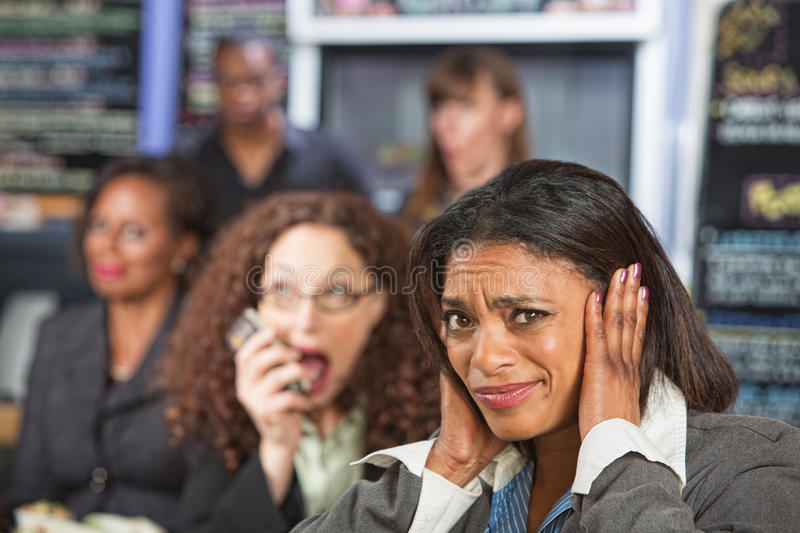 Loud Person on Phone. Bothered business person covering ears while person talks stock image