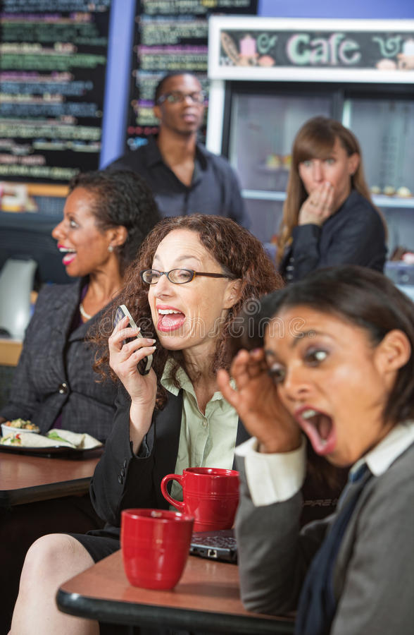 Loud Woman on Phone. Obnoxious women talking loudly on cell phone in cafe stock photo