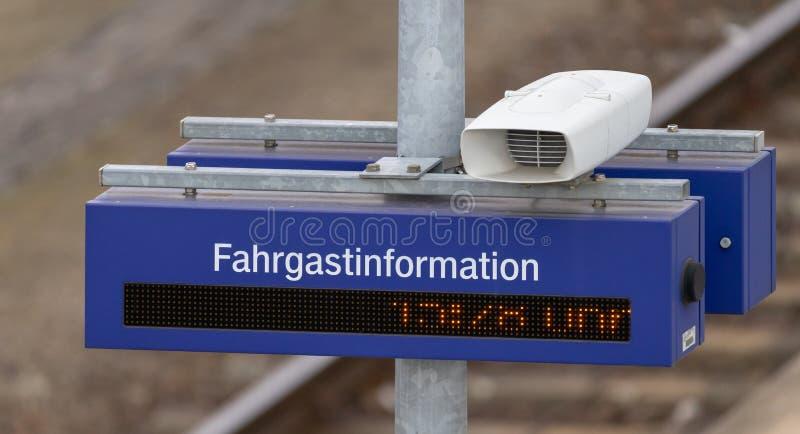 Loudspeaker, digital clock and information board with the German inscription, translation:. `Information for passengers` at a lantern pole on a platform stock images