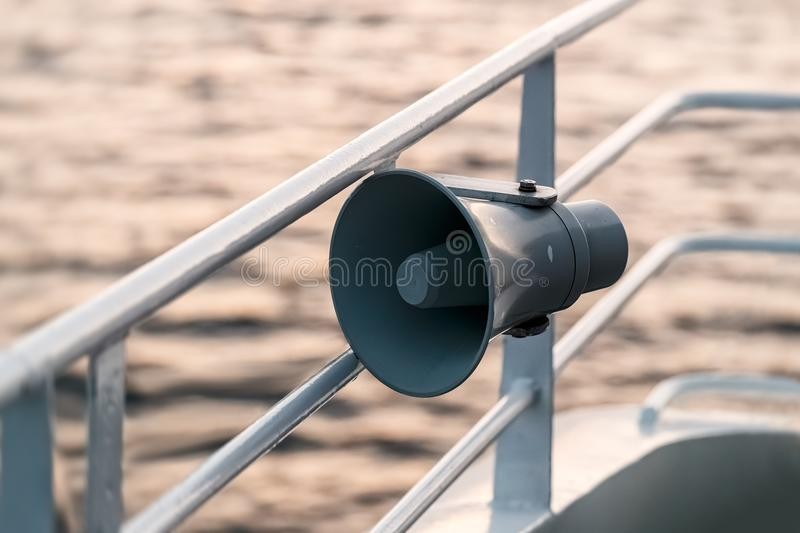 Loudspeaker on ship`s guardrail against sea background. royalty free stock photos