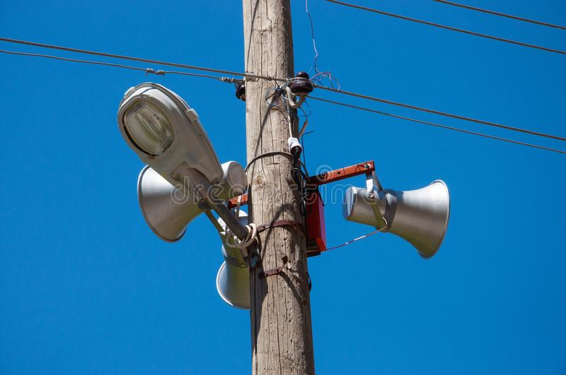 Loudspeakers and street lamp on a pole with electric wires. royalty free stock photo
