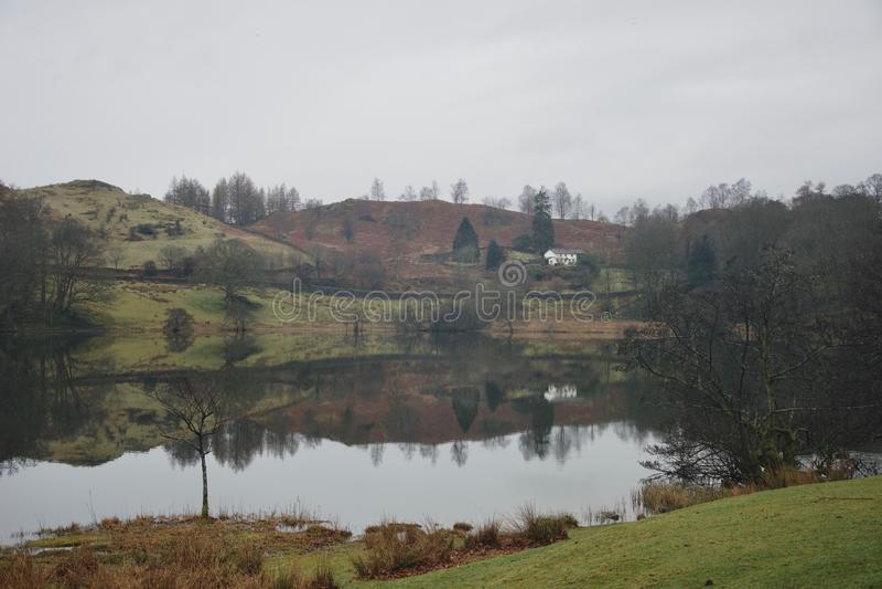 Loughrigg el Tarn: pequeños lago de la montaña y casa de la granja con reflexiones perfectas en el distrito Cumbria del lago foto de archivo