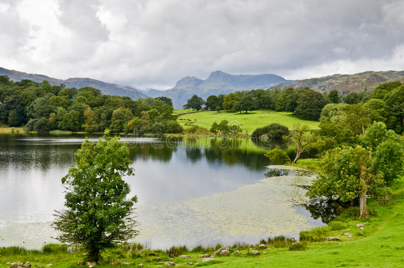 Loughrigg Tarn and the Langdale Pikes. In the English Lake District under a stormy sky royalty free stock photos