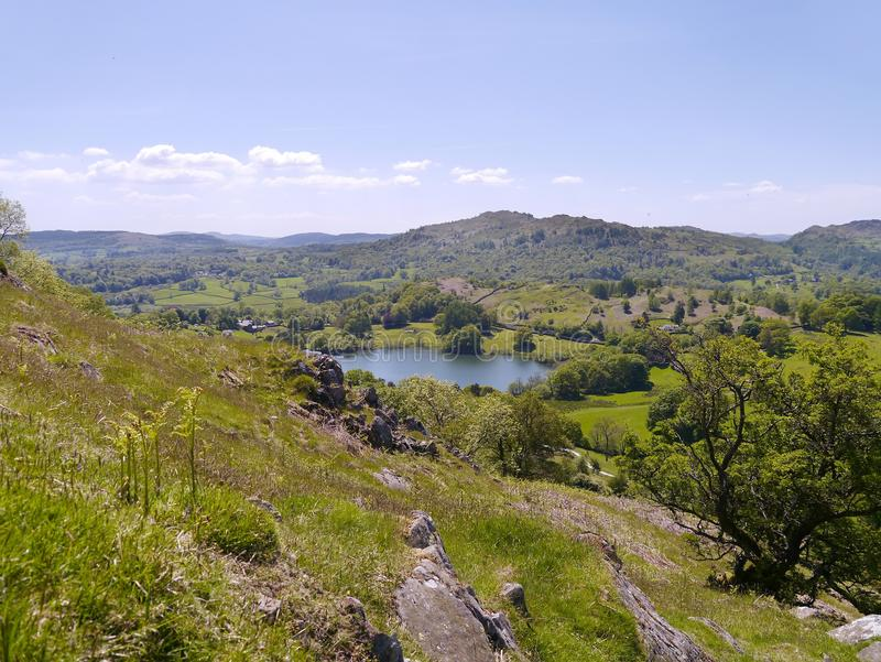 Loughrigg Tarn viewed from hillside. Loughrigg Tarn on a bright summer`s day stock image