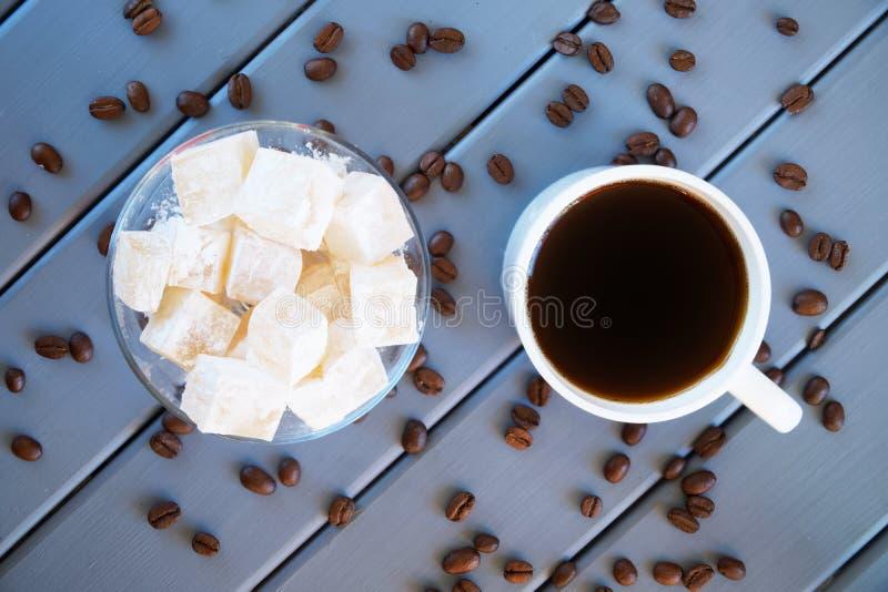 Loukoum branco tradicional clássico - guloseima oriental Copo com café e grões roasted Fundo de madeira fotografia de stock royalty free