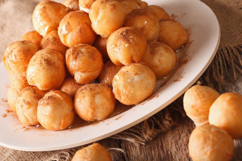 Loukoumades greci del dessert con il primo piano della cannella e del miele Horiz fotografie stock