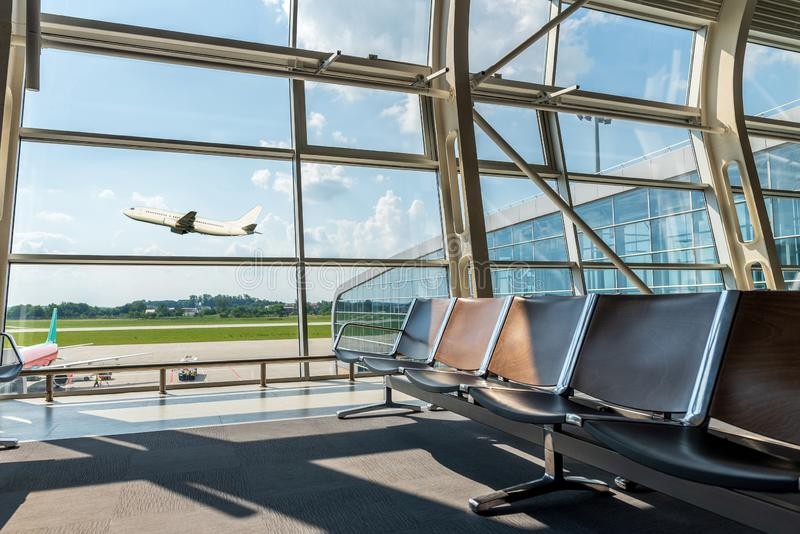 Lounge in airport terminal and passenger plane flying over sky. Summer vacation and travel concept.  stock photo