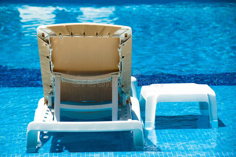 Lounge Chair in the Pool royalty free stock photo