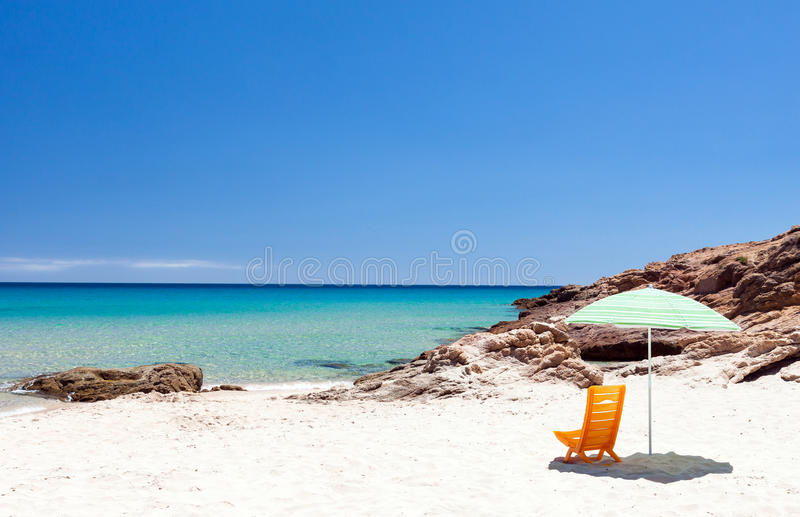 Lounge chair with sun umbrella on a beach. Lonely lounge chair with sun umbrella on a beach in Sardinia, Italy royalty free stock photos