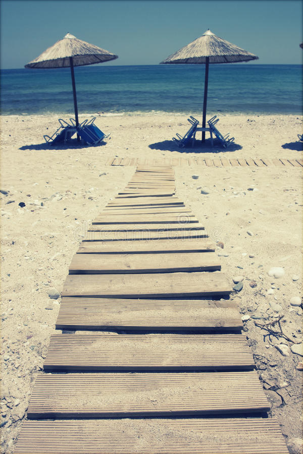 Lounge chairs on the beach - retro style photo royalty free stock images