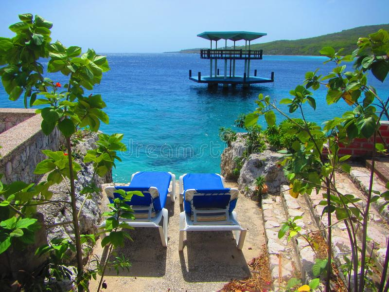 Lounge chairs overlooking the caribbean sea and swim platform. View of lounge chairs on cliff overlooking a swim platform in the Caribbean sea Curacao royalty free stock photo