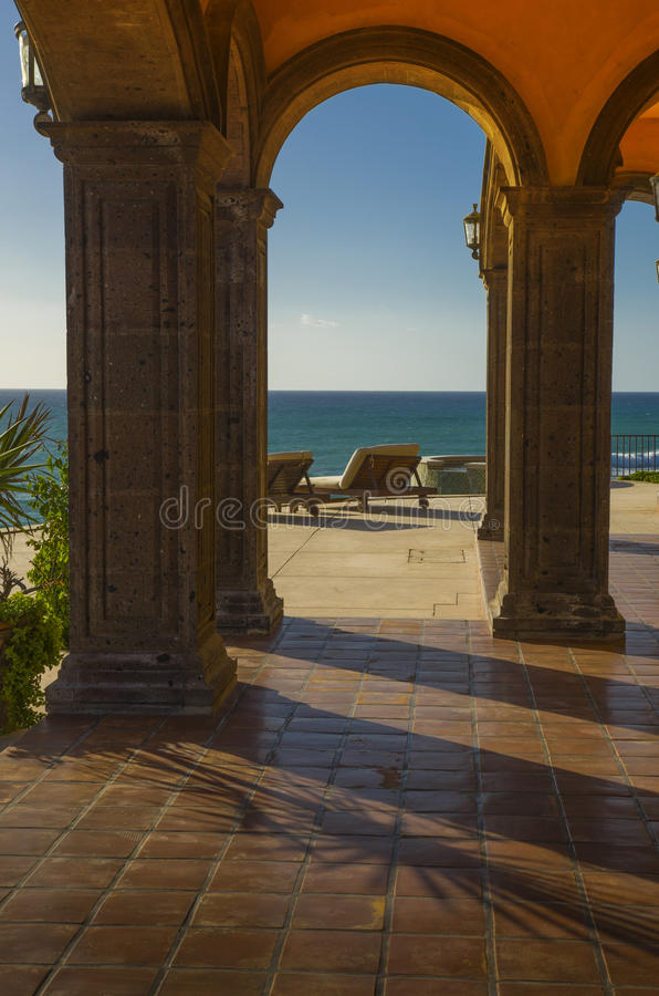 Lounge chairs on a peaceful tropical terrace in Mexico overlooking the Pacific ocean. Lounge beach chairs view the Pacific ocean from a beautiful terrace patio royalty free stock images