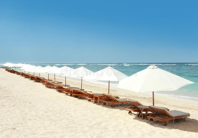Lounge chairs and umbrellas at the beach stock image