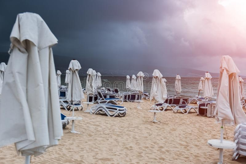 Lounge chairs and umbrellas on empty sand beach.  royalty free stock photo