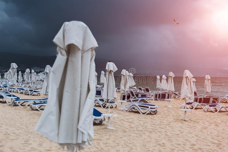 Lounge chairs and umbrellas on empty sand beach vefore the rain with sunlight.  royalty free stock photography