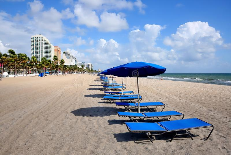 Lounge chairs and umbrellas on Fort Lauderdale Beach. Blue lounge chairs and umbrellas line Fort Lauderdale Beach directly in front of the Atlantic Ocean stock images