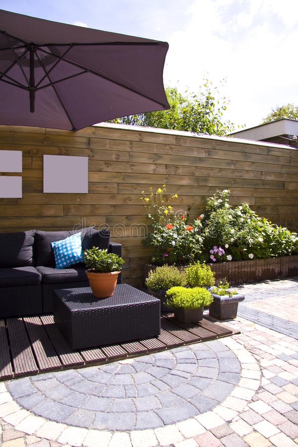 Lounge garden. Lounge furniture on a wooden patio in a lovely garden with plants and flowers stock image