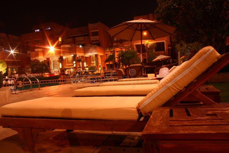 Lounger esterno di legno per la piscina alla notte immagini stock