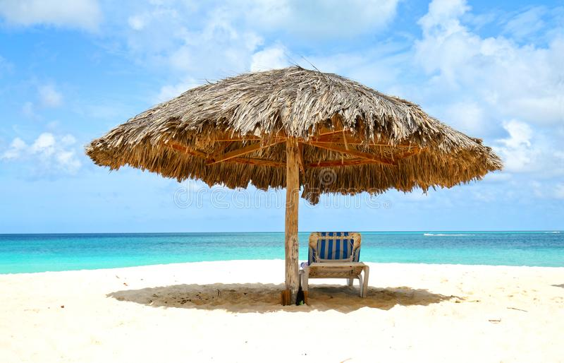 Lounger under cabana, parasol. Blue sea water and dramatic clouds. Oranjestad, Aruba. Famous Eagle Beach stock photos