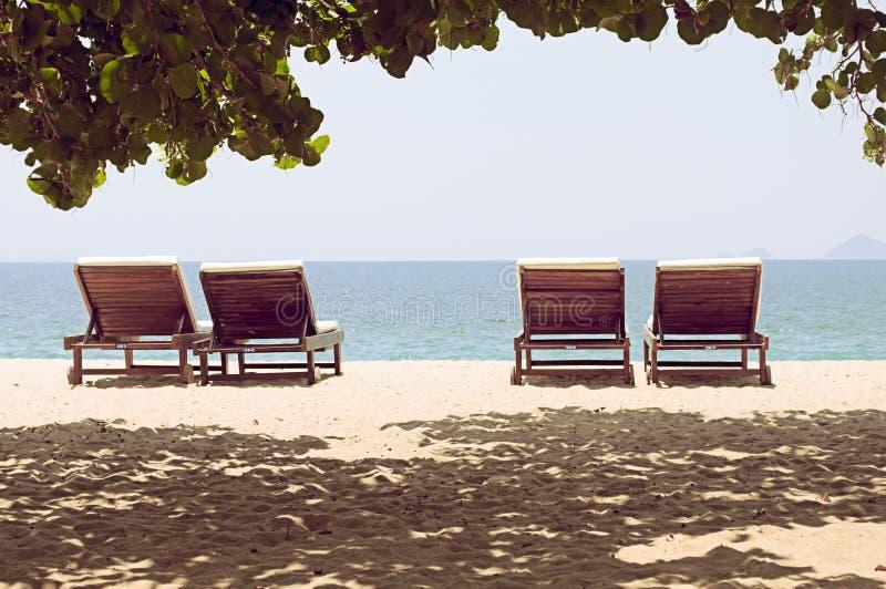4 loungers на дезертированном пляже с целью горизонта стоковое изображение
