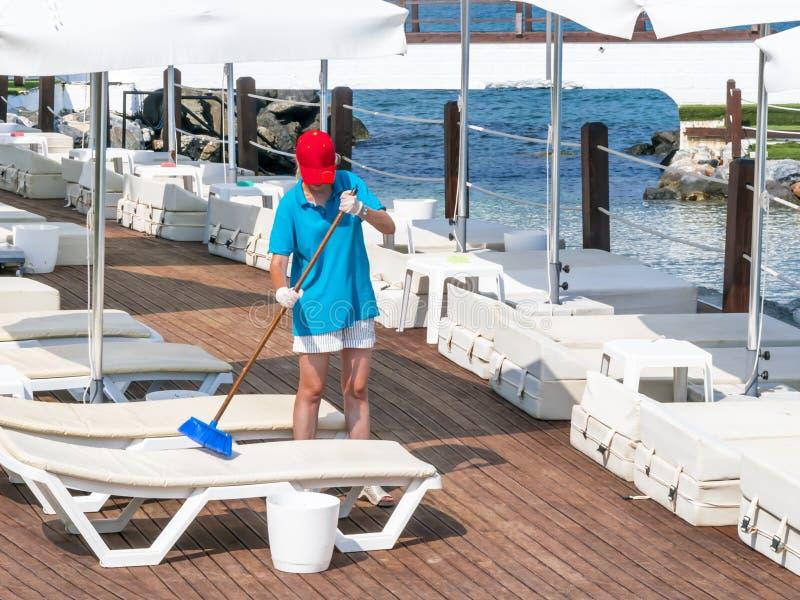 Loungers пляжа лета маленькой девочки очищая Человек работая используя инструменты стоковые изображения rf