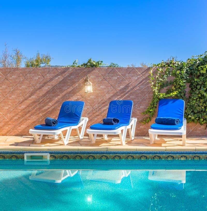 Loungers Солнця бассейном Для путешественников отдыха стоковые изображения