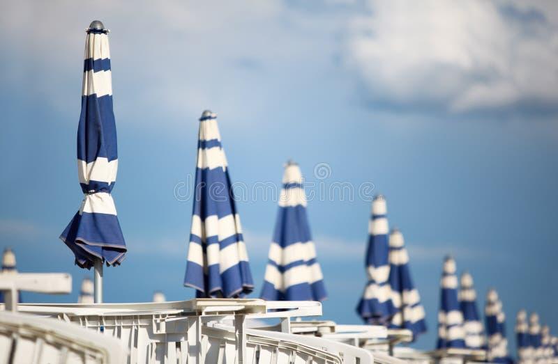 Loungers brancos e guarda-chuvas de praia azuis na praia fotos de stock