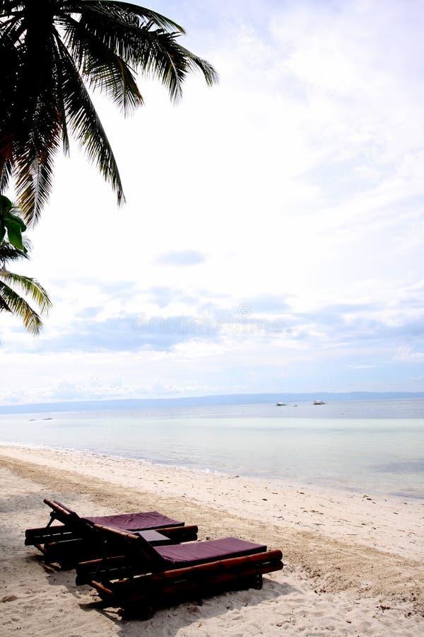 Loungers de Sun na praia fotos de stock royalty free