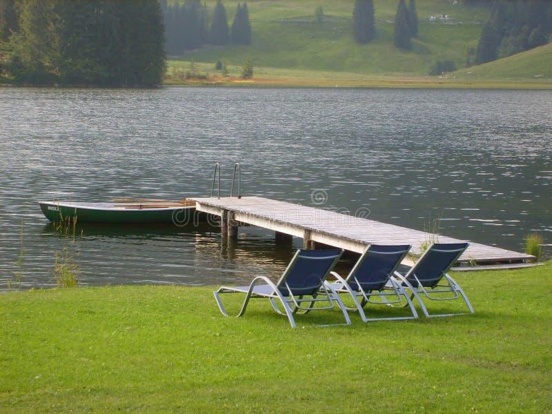 Loungers de Sun pelo lago fotos de stock