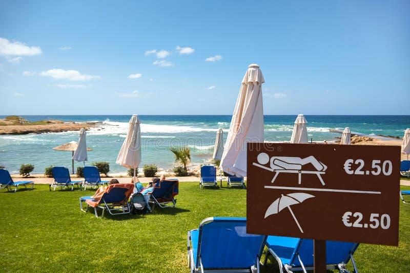 Loungers och paraplyer Hur mycket gör semesterkostnad royaltyfria bilder