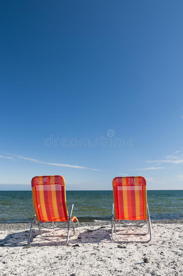Beach Chairs on the Lake. Lounging beach chairs on the Lake Ontario shoreline with large copy space area in the deep blue sky stock photos