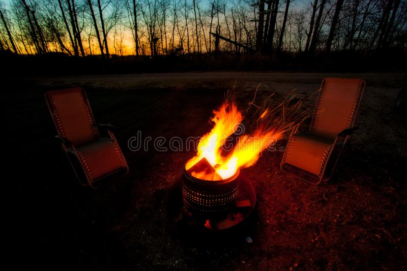 Lounging chairs beside a roaring campfire stock photography