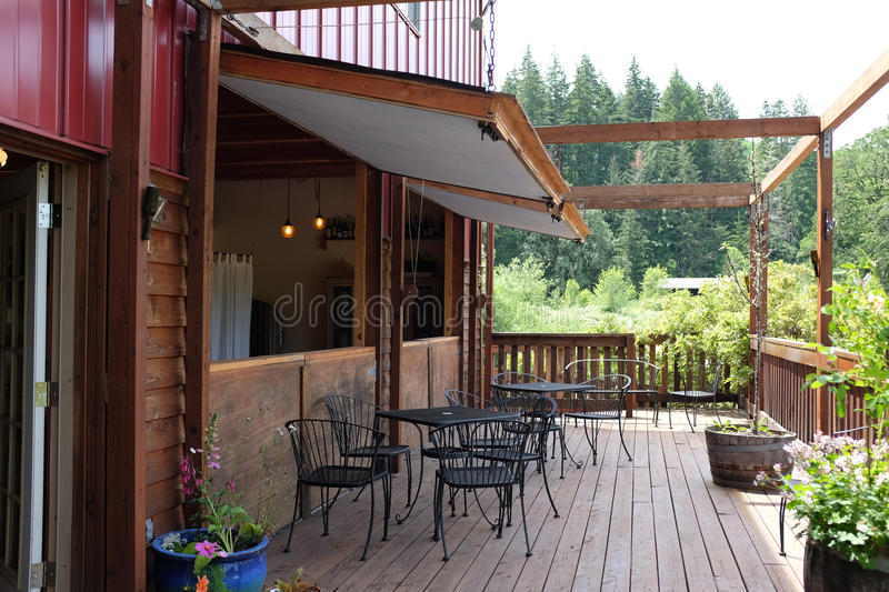 Lounging porch off tasting room at Harris Bridge Vineyard, Oregon. Wren, Oregon, May 2016: Relaxing porch with tables and chairs off the wine tasting room at royalty free stock photos