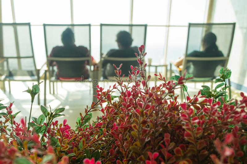 Lounging in spa before treatments. Mood of relaxation; lounging in spa before treatment on cruise ship, looking out windows. Bright red florals in foreground and royalty free stock photography