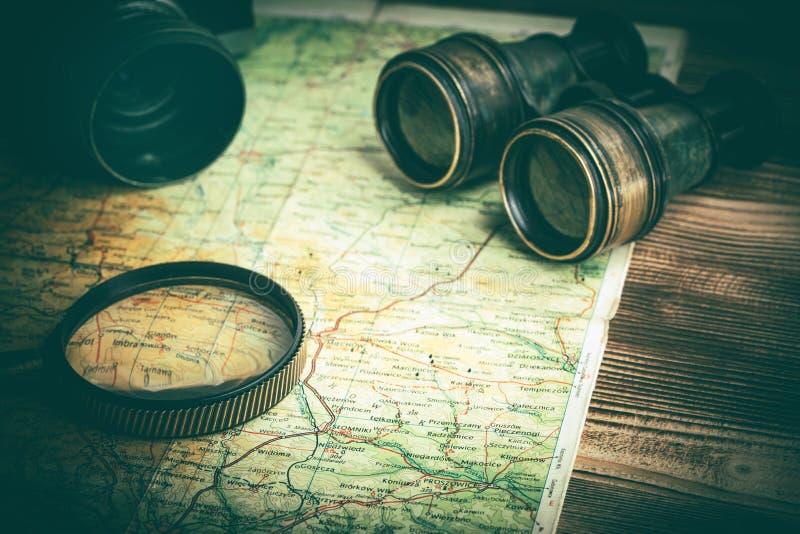 Loupe, appareil-photo et jumelles sur la vieille carte images stock