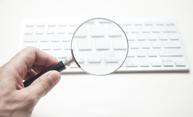Loupe de participation de main avec le clavier d'ordinateur Recherche de l'Internet photo stock