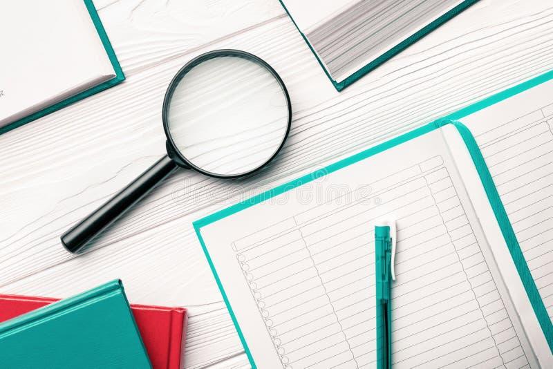 Loupe et bloc-notes avec le stylo bille et livres sur une table en bois blanche comme concept de recherche et de recherche images stock