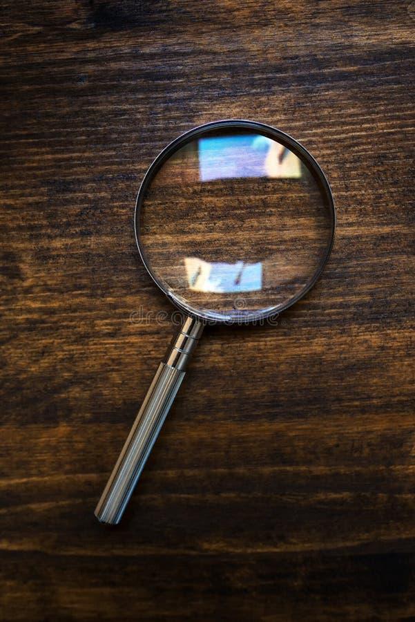 Loupeförstoringsglas på träskrivbordet, bästa sikt fotografering för bildbyråer
