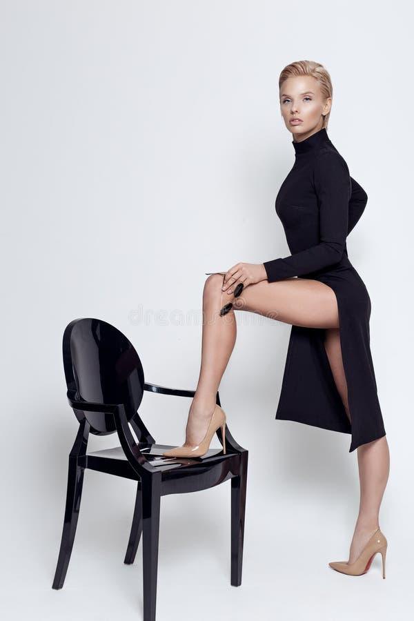 Loura alta e bonita de vestido elegante preto em óculos escuros numa cadeira preta no estúdio sobre fundo branco fotografia de stock royalty free