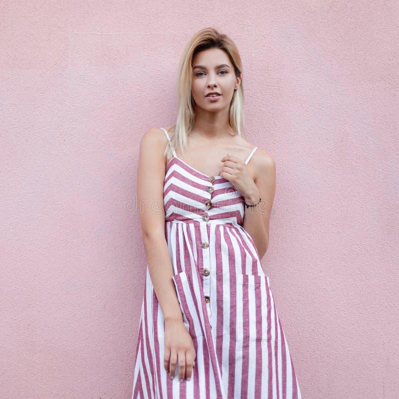 Louro à moda feliz urbano da jovem mulher com sorriso bonito em vestido longo listrado do vintage que levanta perto de uma constr foto de stock royalty free