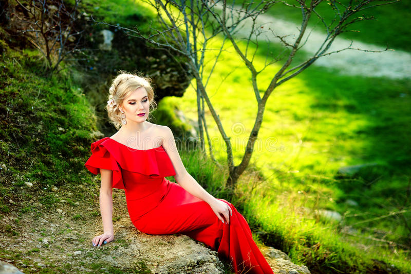 Louro alegre à moda no vestido vermelho que senta-se sob uma árvore em um parque em um dia ensolarado fotografia de stock