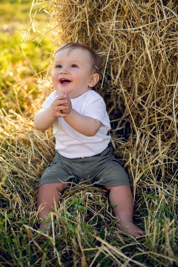 Louro alegre da criança do menino na camiseta de alças branca que senta-se em um campo foto de stock