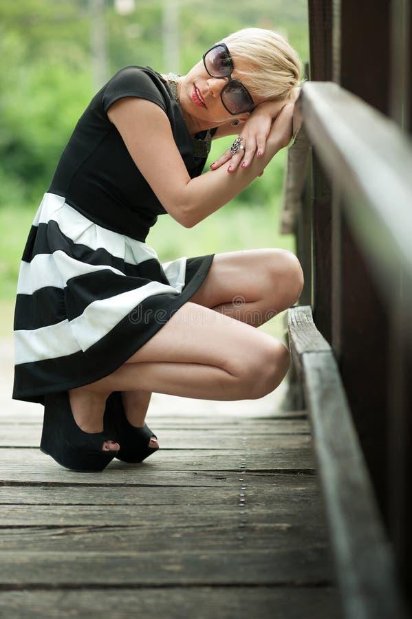 Louro atrativo deprimido na ponte de madeira que agacha-se imagem de stock