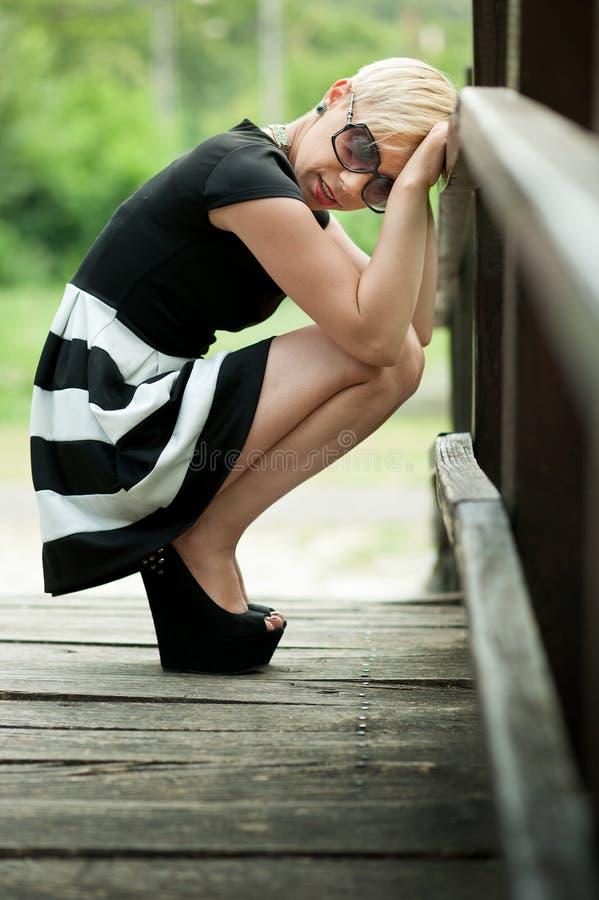 Louro atrativo deprimido na ponte de madeira que agacha-se fotos de stock